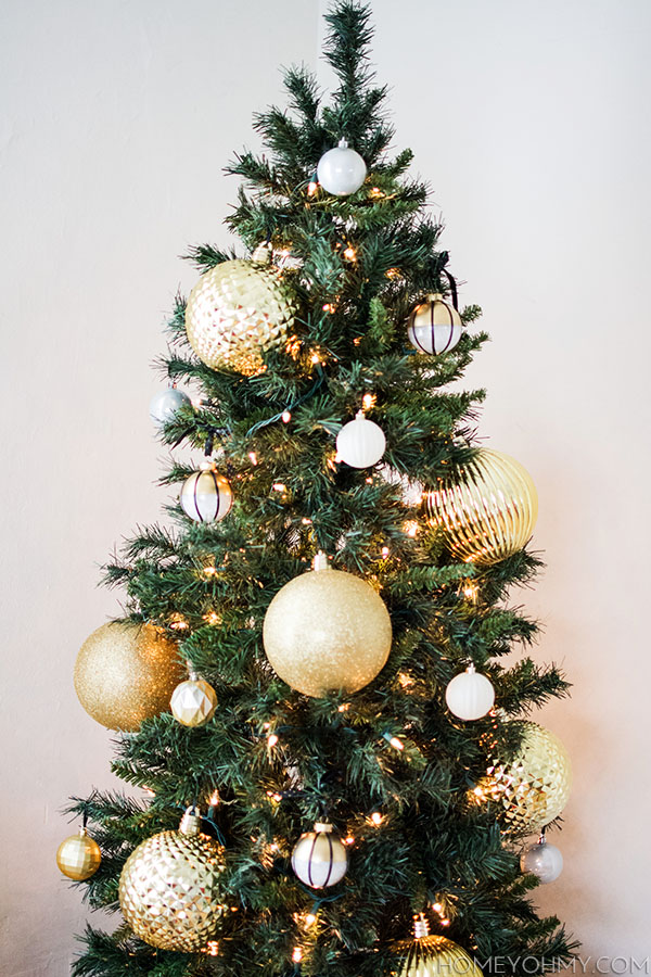 Skinny Christmas tree with large gold ornaments.  Great for big impact in a small space!